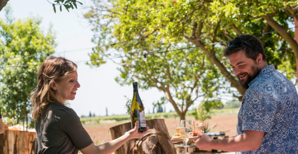 donna in cantina che versa del vino